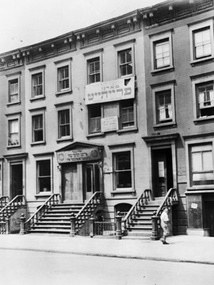 This photograph shows 141-145 East 103rd Street in 1931. The sign just below the top floor reads 'Workers! Your newspaper is the Morgen Freiheit.' The sign over the door reads 'Harlem Jewish Children's School, International Worker's Order.'